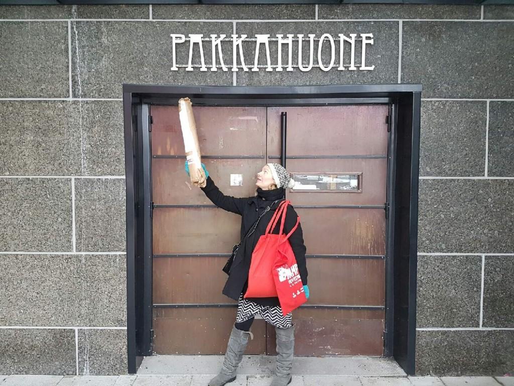 Kelaamo-näytöksen esityspaikka. Saara poseerasi varmin ottein julisteet kädessä ja laukut olalla.