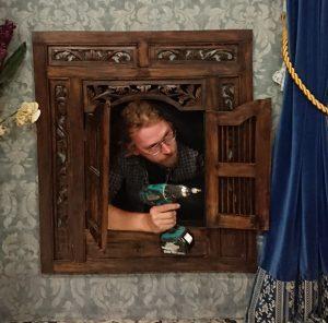 Lavastaja Toppinen kurkistaa lavasteessa olevasta ikkunasta porakoneen kanssa