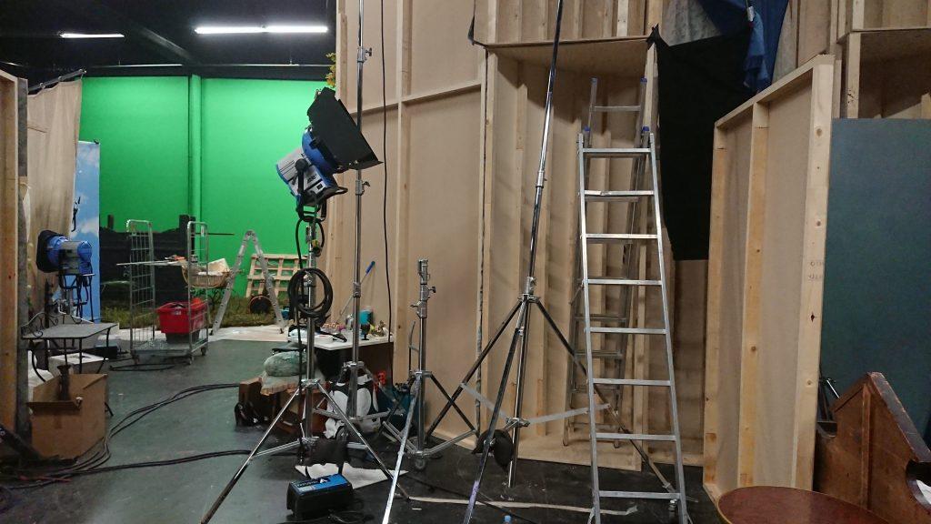 Lavasteen takaa otettu kuva, jossa näkyy studiotilaa ja green screen