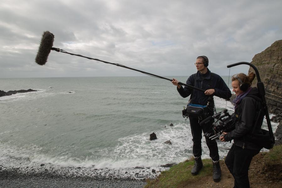 Ohjaaja Antsalo kuvaa ja Äänittäjä Onttonen pitää puomia meren rannalla