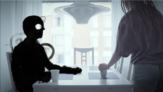 Tumma, piirretty hahmo istuu pöydässä ja pitelee kahvikuppia. Ihmishahmo on istuutumassa pöytään kahvikuppi kädessään.