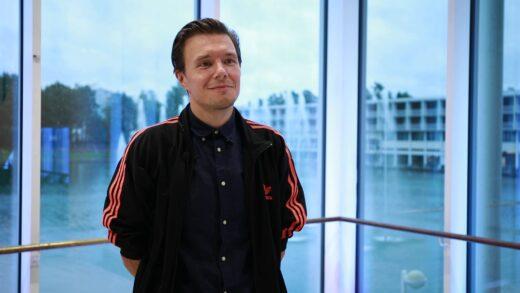 Elokuvaaja Jarmo Kiuru seisoo ikkunan edessä Tapiolan kulttuurikeskuksella